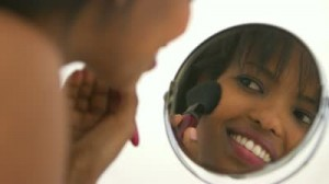 woman looking into make up mirror