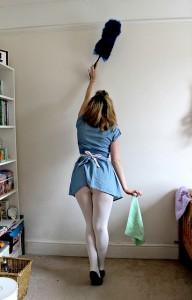 woman dusting wall