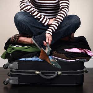 girl sitting on overstuffed suitcase