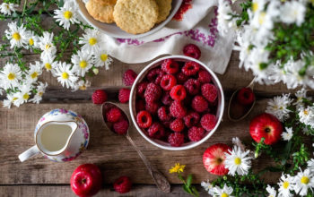 A Raspberry Bowl Surrounded by Flowers