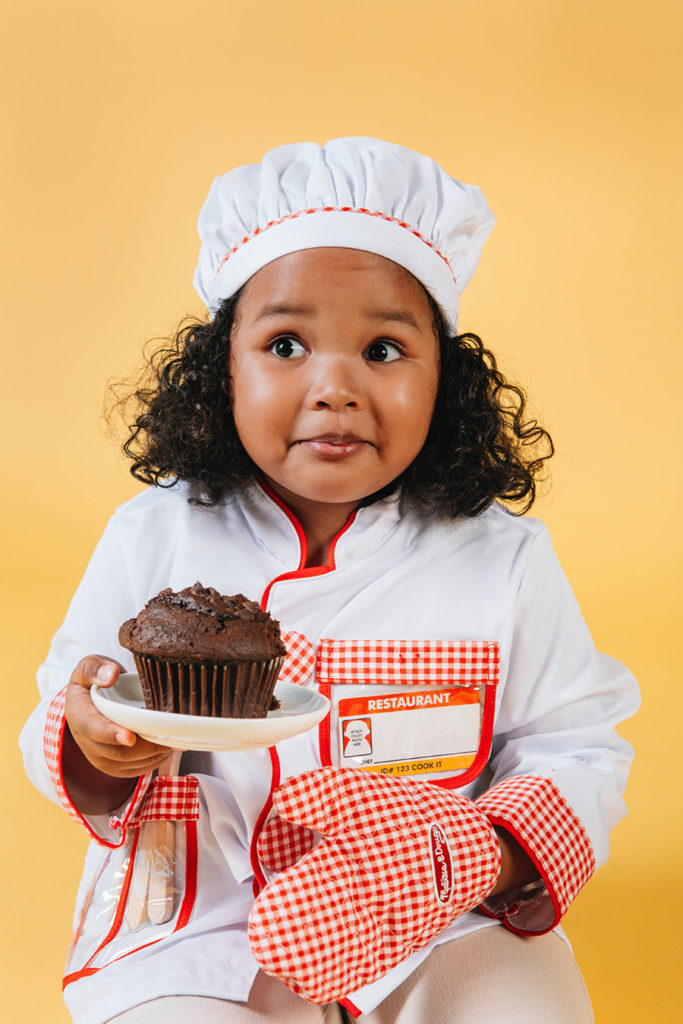 Little Girl Holding Cupcake With An Oven Mitt On One Hand
