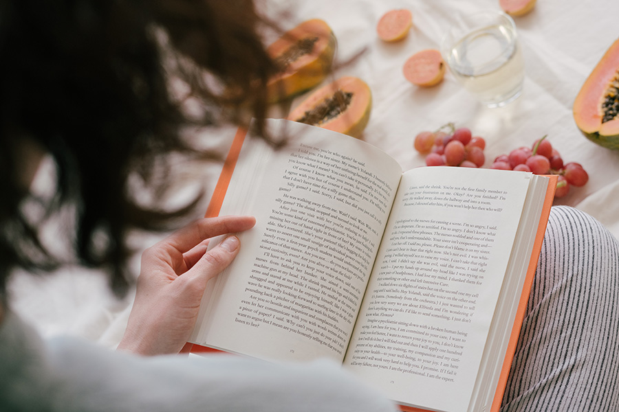 Person Reading a Book Eating Fruit